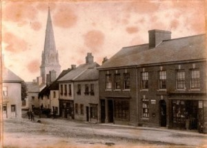 Picture of Uffculme Square, south side with St Mary's Church Spire in background.  Devon.  Undated.